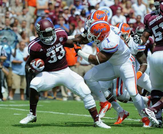 Texas A&M's Christine Michael (33) is stopped by Florida's De'Vante Harris during the first quarter of an NCAA college football game, Saturday, Sept. 8, 2012, in College Station, Texas. Texas A&M begins a new era with its first Southeastern Conference game after leaving the Big 12 Conference. (AP Photo/Dave Einsel) Photo: Dave Einsel, Associated Press / FR43584 AP