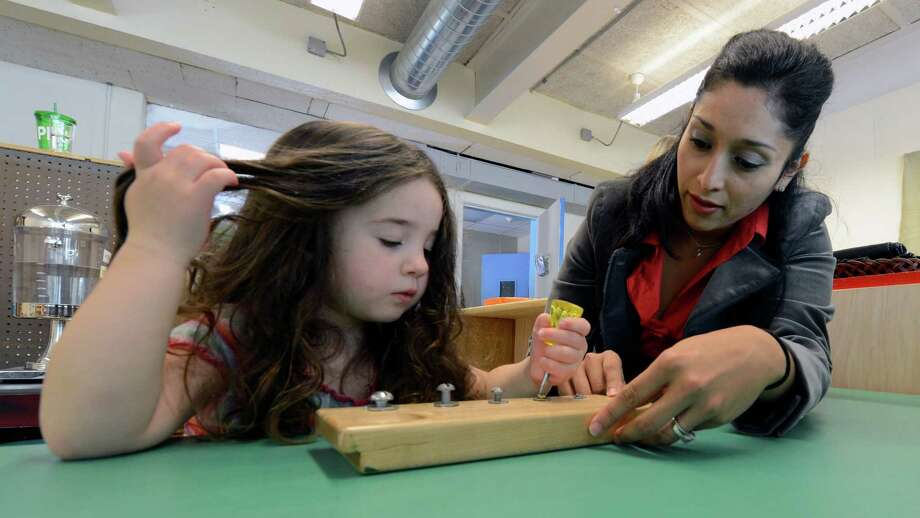 Amelia Kaye, left is given a task using Spanish by instructor Claudia O'Riley at the Boys and Girls Club's Castle Island Bilingual Montessori School in Albany, N.Y. Sept. 25, 2012.    (Skip Dickstein/Times Union) Photo: Skip Dickstein