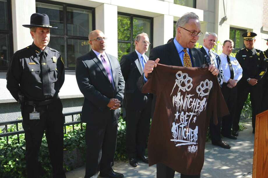 U.S. Sen. Charles Schumer holds a t shirt purchased by the Albany County District Attorney's office from a store on Central Avenue in Albany, during a press conference to discuss the State Witness Protection Act, a Schumer backed bill that would make witness intimidation a federal crime, and toughen sentences for anyone who attempts to intimidate a witness, at the Albany County Judicial Center on Tuesday Sept. 25, 2012 in Albany, NY.   Standing behind him are Albany County Undersheriff William Cox, left, Albany County District Attorney David Soares, second from left, Schenectady County District Attorney Robert Carney, third from left, Rensselaer County District Attorney Richard McNally, third from right, Albany Police Chief Steven Krokoff, second from right,  and Albany County Sheriff Craig Apple. Albany County Executive Dan McCoy is obscured, behind Schumer. (Philip Kamrass / Times Union) Photo: Philip Kamrass / 00019401A