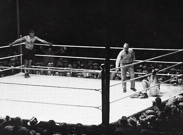 In this Sept. 22, 1927 file photo, referee Dave Berry delivers the count over downed champion Gene Tunney as challenger Jack Dempsey stands in corner at left during their heavyweight title rematch at Soldier's Field in Chicago, Ill.  Tunney tayed down for a nine-count (that turned out to be more than 14 seconds) and went on to win the championship. Photo: Associated Press File Photo