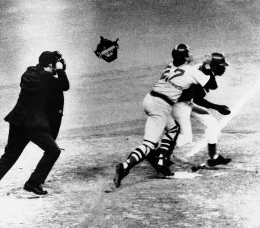 Boston catcher Carlton Fisk (27) claimed interference when he fielded Ed Armbrister's bunt, then collided with him before throwing to second in an attempt to nail Cesar Geronimo, Oct. 15, 1975, in Cincinnati. The throw sailed over the head of second baseman Denny Doyle, setting up the winning run for Cincinnati and giving them a 2-1 lead in the World Series. Photo: Stan Denny, Associated Press File Photo / AP1975