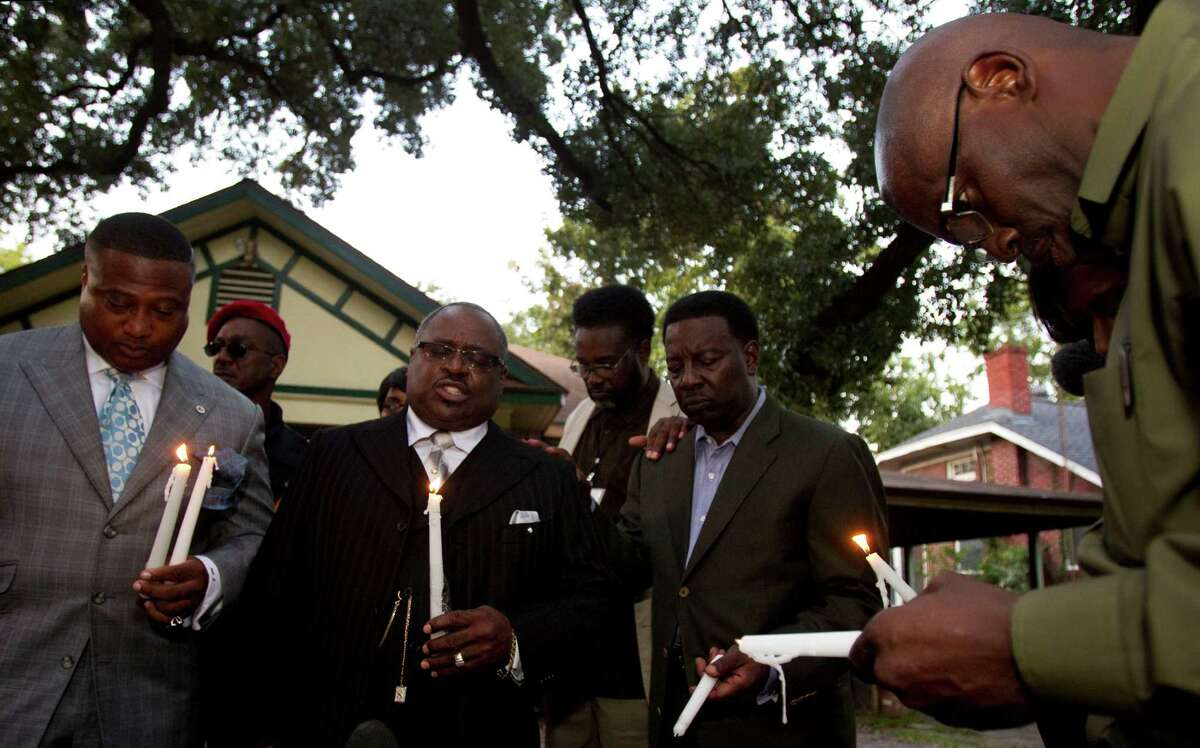 The Rev. Ronald Smith, second from left, leads a prayer on Tuesday evening outside the personal care home where Brian Claunch, a mentally ill double amputee, was shot and killed by a Houston police officer last week.
