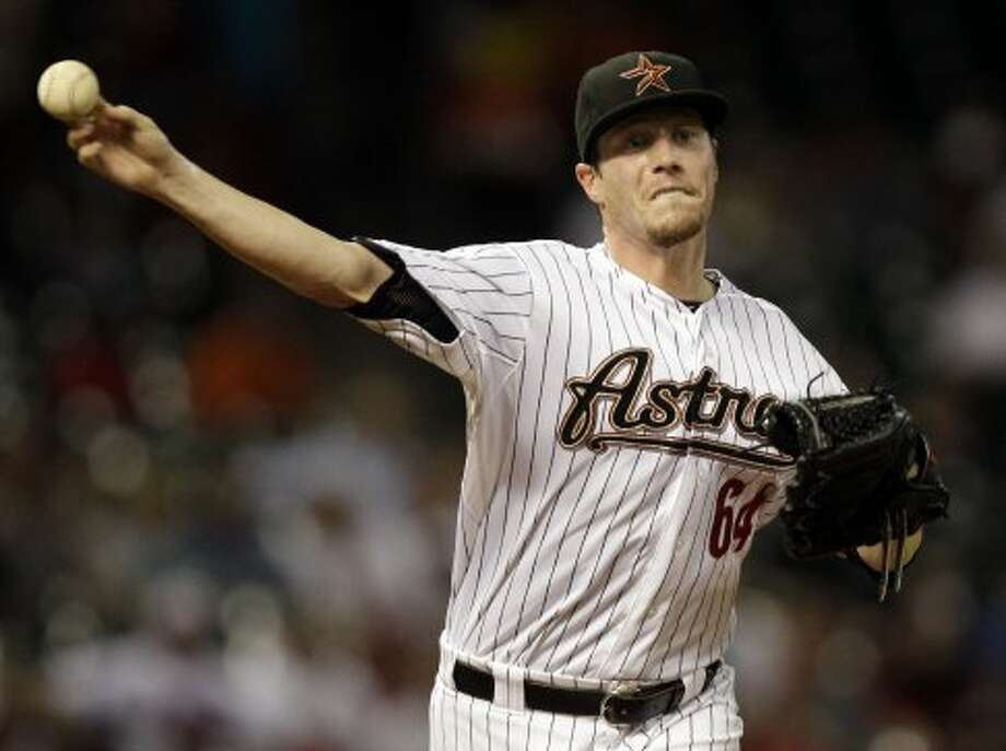 Astros pitcher Lucas Harrell throws to first base during the first inning. (Melissa Phillip / © 2012 Houston Chronicle)