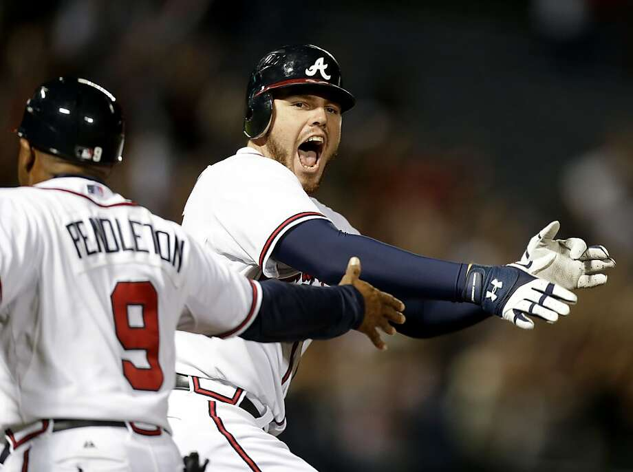Atlanta Braves' Freddie Freeman, right, celebrates while running past first base coach Terry Pendleton after hitting a home run in the ninth inning to beat the Miami Marlins. Photo: David Goldman, Associated Press
