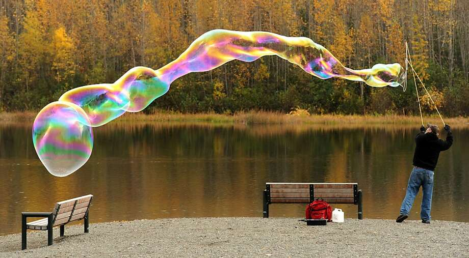 Jay Hiner creates giant bubbles using a home-made wand and non-toxic solution Tuesday, Sept. 25, 2012, at Cheney Lake in east Anchorage, Alaska. Photo: Erik Hill, Associated Press