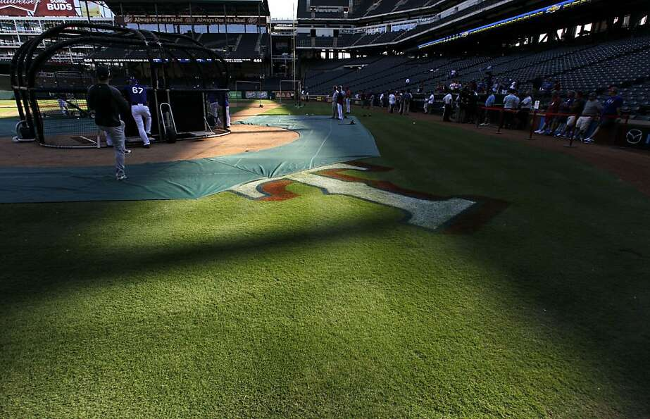 A ray of sunlight shines across the Texas Rangers logo behind home plate before  a baseball game