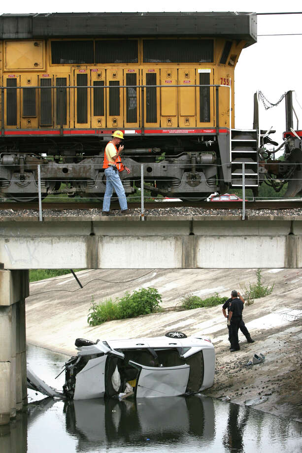 San Antonio firefighters inspect the wreckage of a car that was hit by a Union Pacific train at West Summit Avenue at the tracks near Interstate 10, Friday, May 23, 2008. The driver of the car was transported to the hospital. Photo: Bob Owen, San Antonio Express-News / rowen@express-news.net