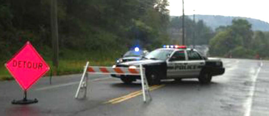 Police stand watch near Candlewood Lake Road North in New Milford Wednesday morning as police search for a person who shot someone about 1 a.m. near Rocky River Inn along Kent Road (Route 7 North). The road was temporarily closed from Candlewood Lake Road North to Boardman Road during the search. Sept. 26, 2012   Photo by Libor Jany Photo: Contributed Photo