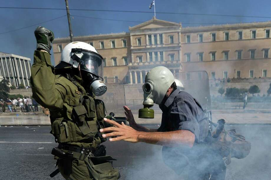 TOPSHOTS Demonstrators clash with riot police on September 26, 2012 in Athens during clashes with demonstrators at a 24-hours general strike. Police in Athens clashed with hooded youths throwing firebombs on the sidelines of a large demonstration against a new round of austerity cuts.    AFP PHOTO / ARIS MESSINISARIS MESSINIS/AFP/GettyImages Photo: ARIS MESSINIS, AFP/Getty Images / AFP