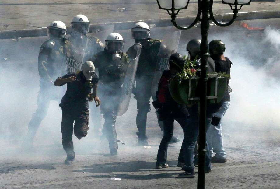 Riot police officers try to arrest a masked demonstrator during clashes in Athens, Wednesday Sept. 26, 2012. Police clashed with protesters hurling petrol bombs and bottles after an anti-government rally called as part of a general strike in Greece turned violent. About 50,000 people joined the union-organized march held during a general strike against new austerity measures planned in the crisis-hit country. Photo: Dimitri Messinis, AP / AP