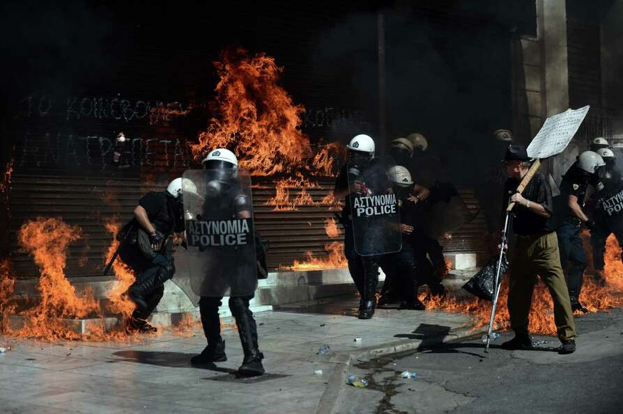 TOPSHOTS A fire bomb explodes behind a riot police squad on September 26, 2012 in Athens during clas