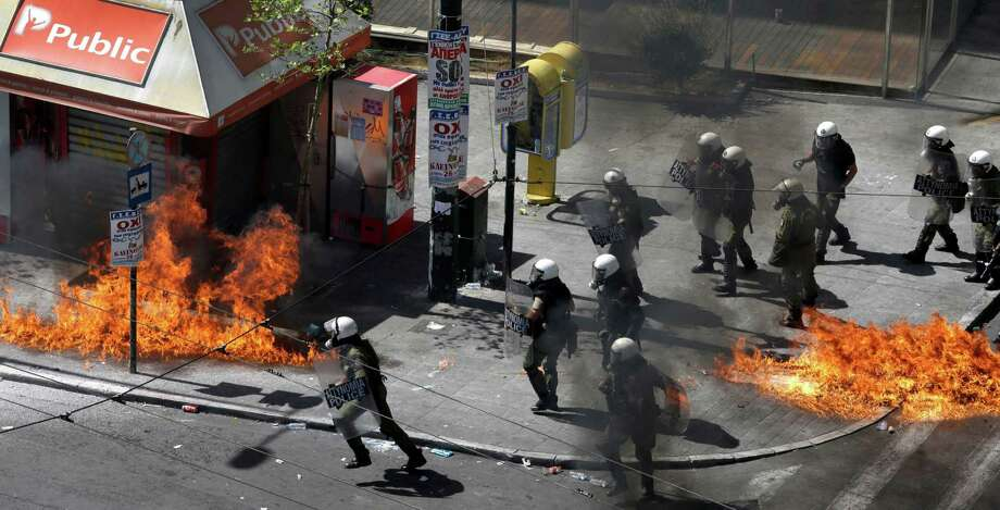 A fire bomb explodes among riot police during clashes in Athens Wednesday Sept. 26, 2012. Police clashed with protesters hurling petrol bombs and bottles in central Athens Wednesday after an anti-government rally called as part of a general strike in Greece turned violent. Photo: Dimitri Messinis, AP / AP
