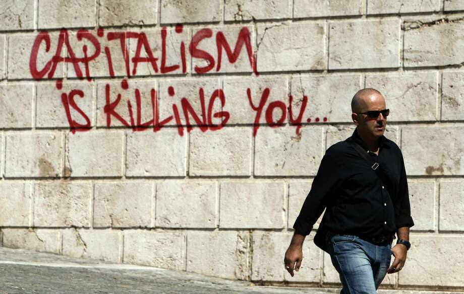 A pedestrian walks in front of graffiti in Athens, Tuesday, Sept. 25, 2012. Unions have called a nationwide general strike Wednesday to protest new austerity measures being hammered out between the government and Greece's international creditors to ensure the country continues receiving emergency loans that have kept it afloat since 2010. Photo: Thanassis Stavrakis, AP / AP