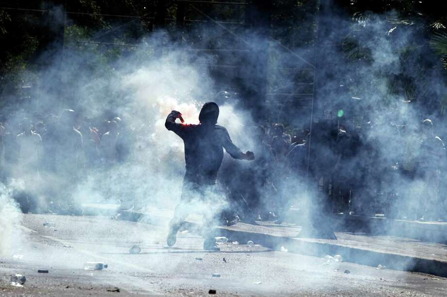 Demonstrators clash with riot police on September 26, 2012 in Athens during a 24-hours general strike. Police in Athens clashed with hooded youths throwing firebombs on the sidelines of a large demonstration against a new round of austerity cuts.    AFP PHOTO /  PANAGIOTIS TZAMAROSPanagiotis Tzamaros/AFP/GettyImages Photo: PANAGIOTIS TZAMAROS, AFP/Getty Images / AFP