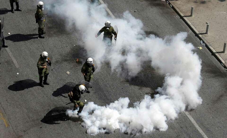 A riot police officer kicks a tear gas canister during clashes in Athens, Wednesday Sept. 26, 2012.