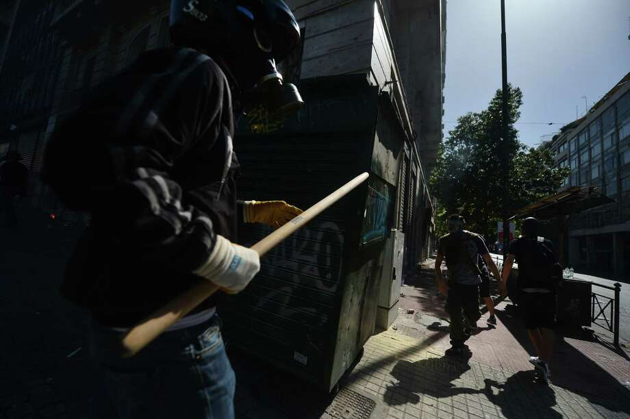 Demonstrators clash with riot police on September 26, 2012 in Athens during clashes with demonstrators at a 24-hours general strike. Police in Athens clashed with hooded youths throwing firebombs on the sidelines of a large demonstration against a new round of austerity cuts.    AFP PHOTO / ARIS MESSINISARIS MESSINIS/AFP/GettyImages Photo: ARIS MESSINIS, AFP/Getty Images / AFP