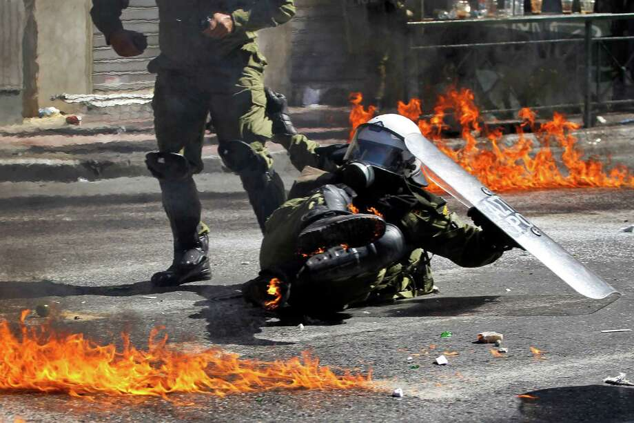 A riot policeman reacts after he was hit by a petrol bomb thrown by protesters during a nationwide general strike in Athens, Wednesday, Sept. 26, 2012. Police clashed with protesters hurling petrol bombs and bottles in central Athens Wednesday after an anti-government rally called as part of a general strike in Greece turned violent. Photo: Petros Giannakouris, AP / AP