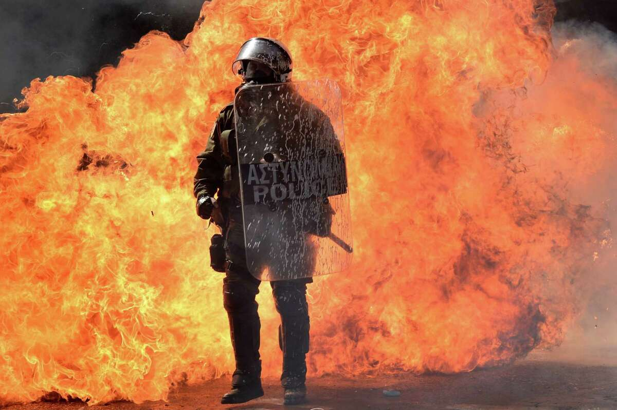 A riot police officer stands in front of burning firebombs on September 26, 2012 in Athens during a 24-hours general strike. Police in Athens clashed with hooded youths throwing firebombs on the sidelines of a large demonstration against a new round of austerity cuts. AFP PHOTO / ARIS MESSINISARIS MESSINIS/AFP/GettyImages