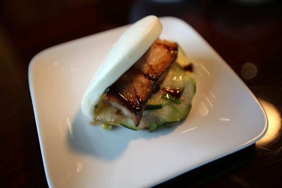 The Pork Pocket is a Chinese steamed bun sandwich filled with slow roasted pork belly, cucumber sonomono, scallion and hoisin sauce at Sushi Express located on Stone Oak Parkway, Tuesday, Dec. 6, 2011. JERRY LARA/glara@express-news.net (San Antonio Express-News)