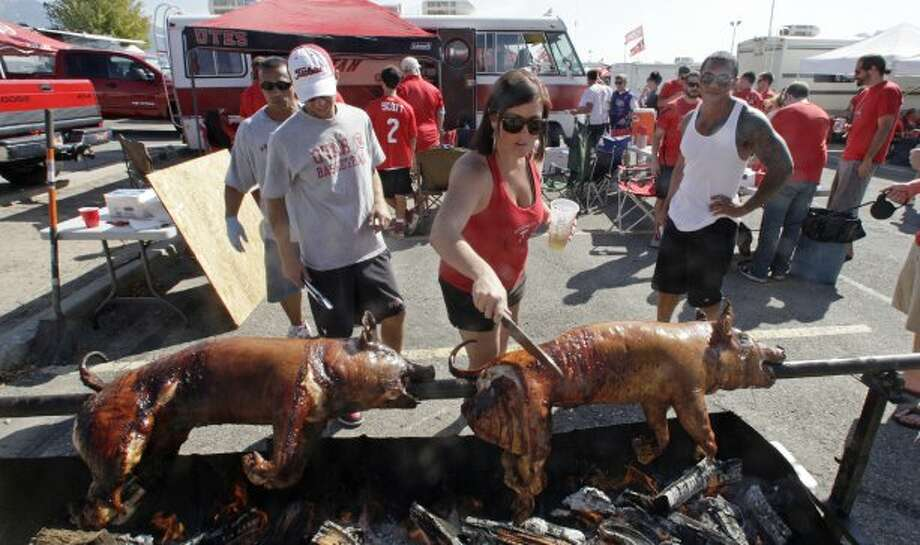 Utah fans roast several pigs during a tailgate party before an NCAA college football game between BYU and Utah on Saturday, Sept. 15, 2012, in Salt Lake City. (AP Photo/Rick Bowmer) (Associated Press)
