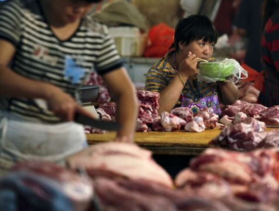 A pork vendor eats breakfast as she waits for customers at a market in Fuyang in central China's Anhui province Sunday, Sept. 9, 2012. A jump in food prices pushed China's inflation rate to rise 2 percent in August compared with a year earlier, complicating efforts by the government to revive growth with further stimulus measures. (AP Photo) CHINA OUT (Associated Press)