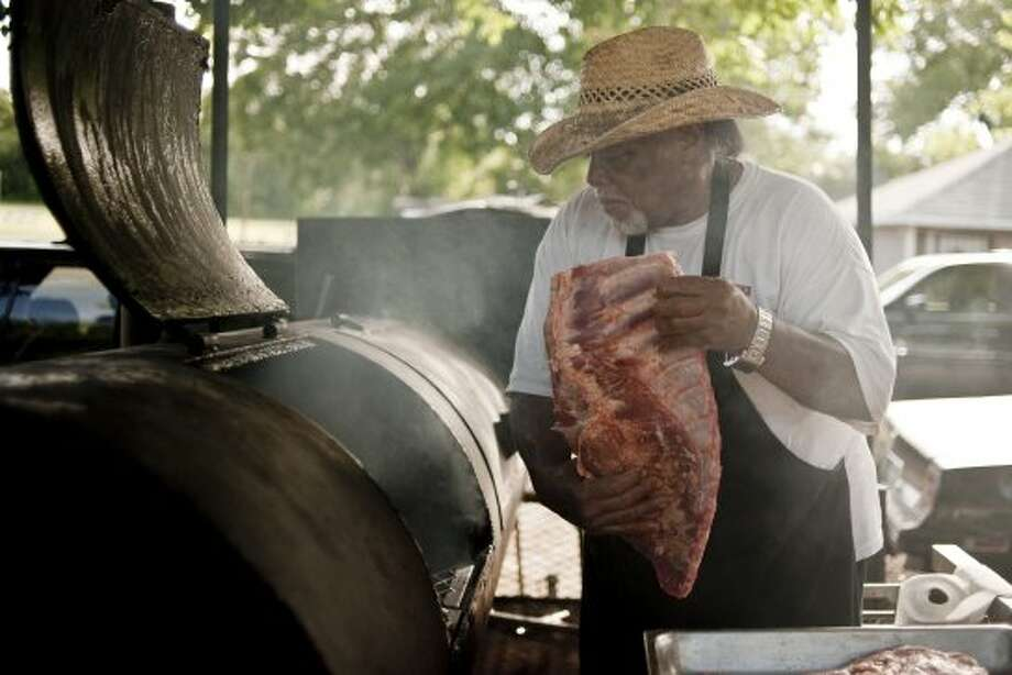 Pitmaster Clyde Biggins hoists a rack of pork ribs onto his largest smoker in front of his Dallas house on July 26, 2012 to smoke overnight. Biggins is trying to make a comeback on the North Texas barbecue scene.  (AP Photo/The Dallas Morning News, Jeff Lautenberger) (Associated Press)
