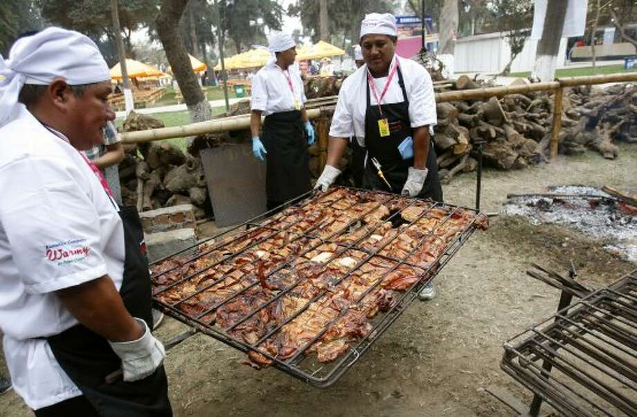 Cooks carry a grill with the Peruvian pork dish called 'Chancho al palo' or pork on a stick at the inauguration of the 5th edition of Peru's Mistura International Gastronomic Fair, in Lima, Peru, Thursday, Sept. 6, 2012. According to the organizers, 600,000 people are expected to attend the 10-day festival featuring typical Peruvian food. (AP Photo/Karel Navarro) (Associated Press)
