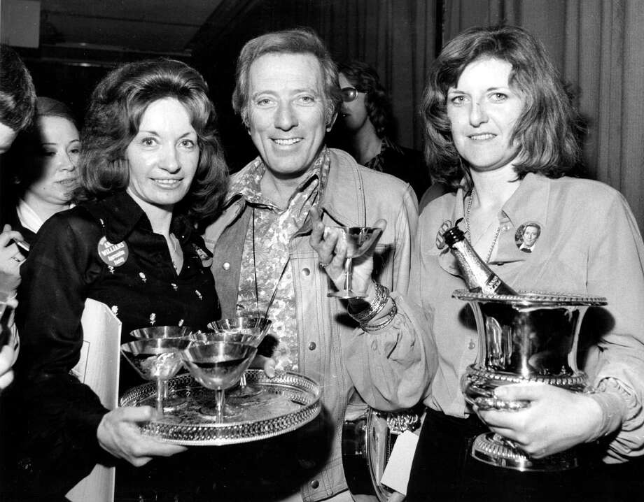 30th April 1974:  Popular American singer Andy Williams receives a silver ice bucket, goblets and a tray from Marilyn Everson, right, and Penny Probert, president and vice-president, respectively, of the Andy Williams Appreciation Society, at the Kensington Close Hotel. Photo: Central Press, Getty Images / Hulton Archive
