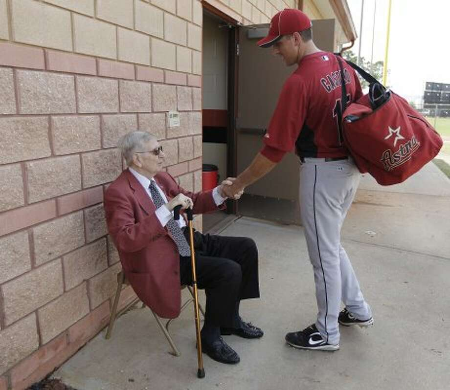 Hall of Fame broadcaster, Milo Hamilton greets Houston Astros catcher Jason Castro (15) as he walks back to the clubhouse in 2011. (Karen Warren / Houston Chronicle)