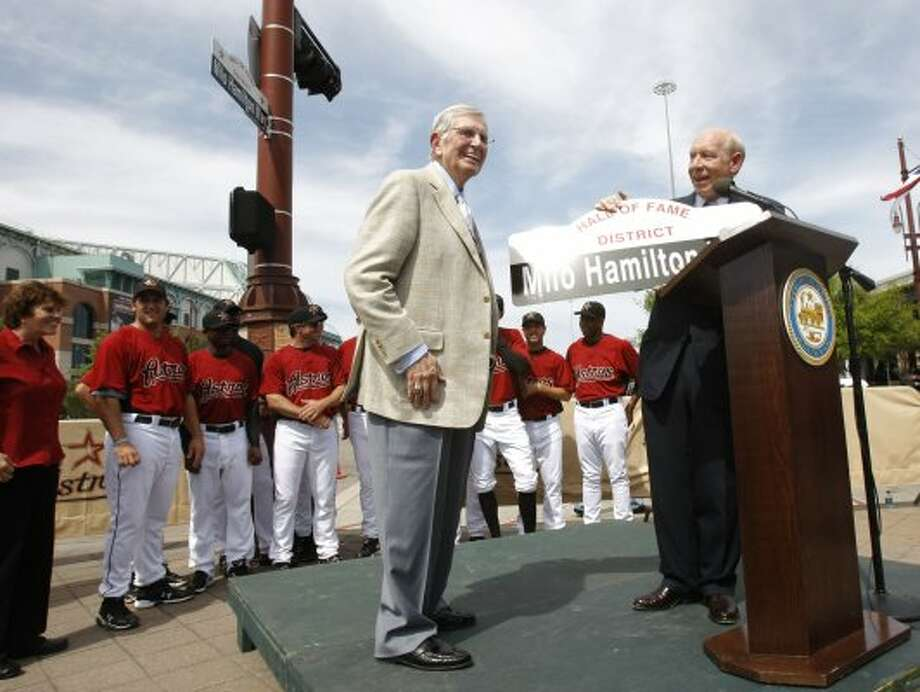 Astros announcer Milo Hamilton, left, who is in the Hall of Fame for his 64 years of sports broadcasting, gets a copy of his street sign from Houston Mayor Bill White at a celebration at the old Hamilton and Texas streets intersection in Downtown Houston in 2009. A street at the intersection was given the name Milo Hamilton Way near Minute Maid Park. (Julio Cortez / Houston Chronicle)