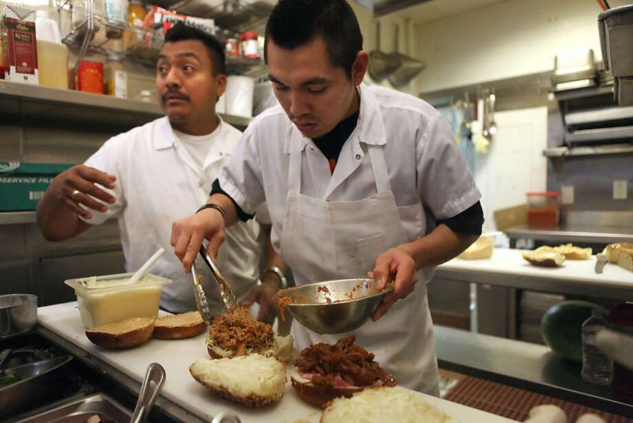Sous chef Luis Euan (above left) and prep cook Angel Pech fill a lunchtime order at Golden West, where the short rib sandwich (far right) has been on the menu since day one, and folks line up for walk-up service if they need a quick pick-me-up. Photo: Liz Hafalia, The Chronicle