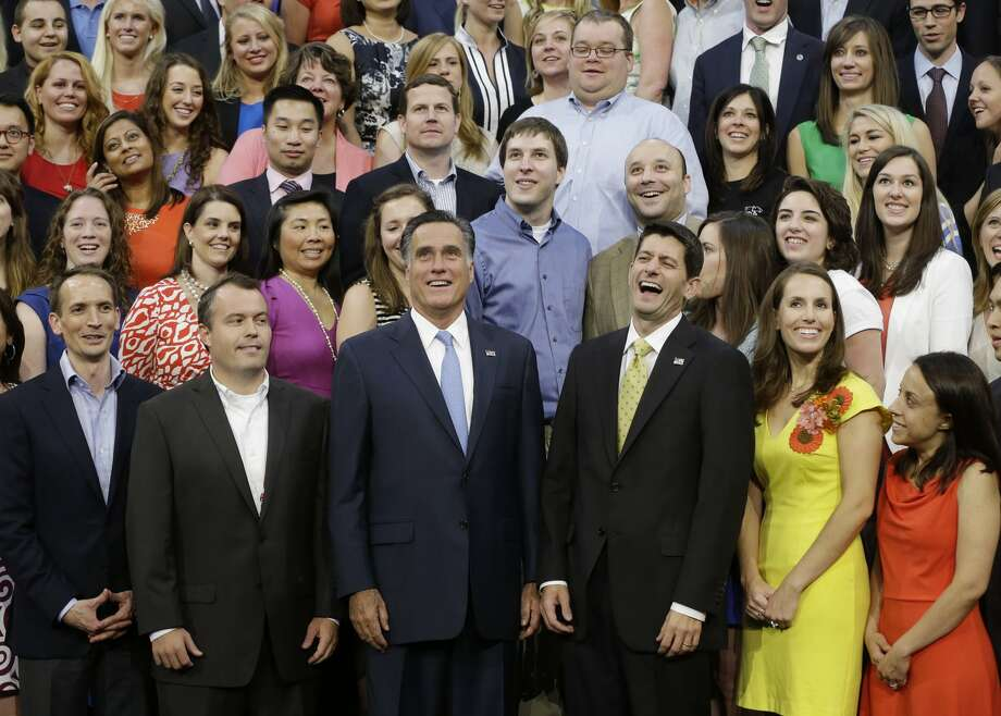 Republican presidential nominee Mitt Romney and Republican vice presidential nominee, Rep. Paul Ryan pose with their campaign staff for a group picture at the Republican National Convention in Tampa, Fla., on Thursday, Aug. 30, 2012.(AP Photo/Charles Dharapak) (Associated Press)
