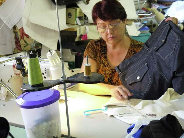 Lety Garza works on a pair of organic denim jeans that will be worn in Fuerza Unida's fashion show Saturday. Photo: Michael Quintanilla, San Antonio Express-News