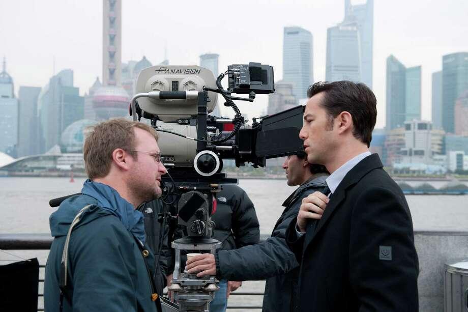 "Director-writer Rian Johnson, left, and Joseph Gordon-Levitt talk on the set of the action thriller ""Looper."" Photo: Courtesy Of Sony Pictures Entert, LOOPER / © 2012 Looper, LLC. All rights reserved."