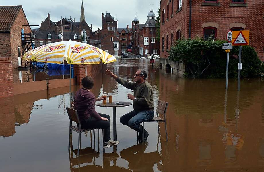 Soggy ol' England: Brits enjoy a couple of pints in flooded York,
