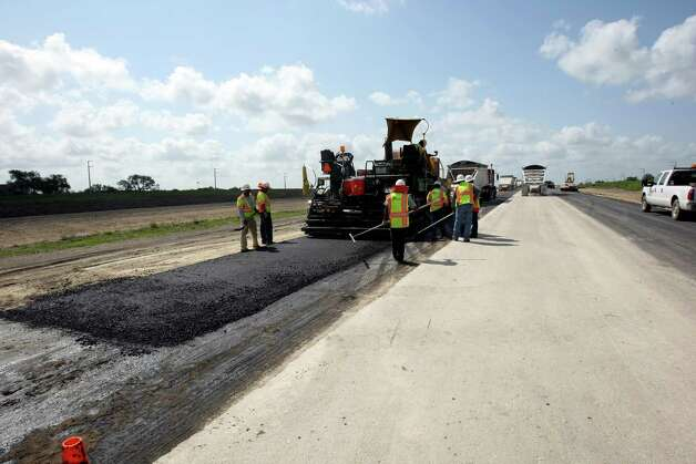 Workers pave a section of Texas 130 on Monday July 23, 2012.  The road is the state's first public-private toll road, opens this fall, ending in Seguin at I-10.  It will be the first toll road near San Antonio. Part of Texas 130, which was built by the state, is already open, from Georgetown to just south of Austin. The new section is being built by the private company Cintra-Zachary. Photo: Helen L. Montoya, SAN ANTONIO EXPRESS-NEWS / ©2012 SAN ANTONIO EXPRESS-NEWS