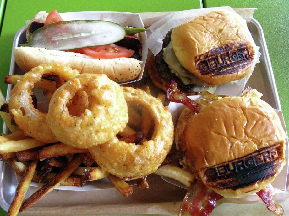 This order at BurgerFi consists of (clockwise from top left) the Chicago Dog, Breakfast Burger, Ultimate Cheeseburger, and fries/onion rings. Photo: Jennifer McInnis, San Antonio Express-News
