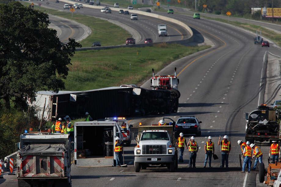 An overturned 18-wheeler blocks traffic north of New Braunfels, shutting down all I-35 southbound lanes, on Wednesday. Photo: Lisa Krantz, San Antonio Express-News / San Antonio Express-News