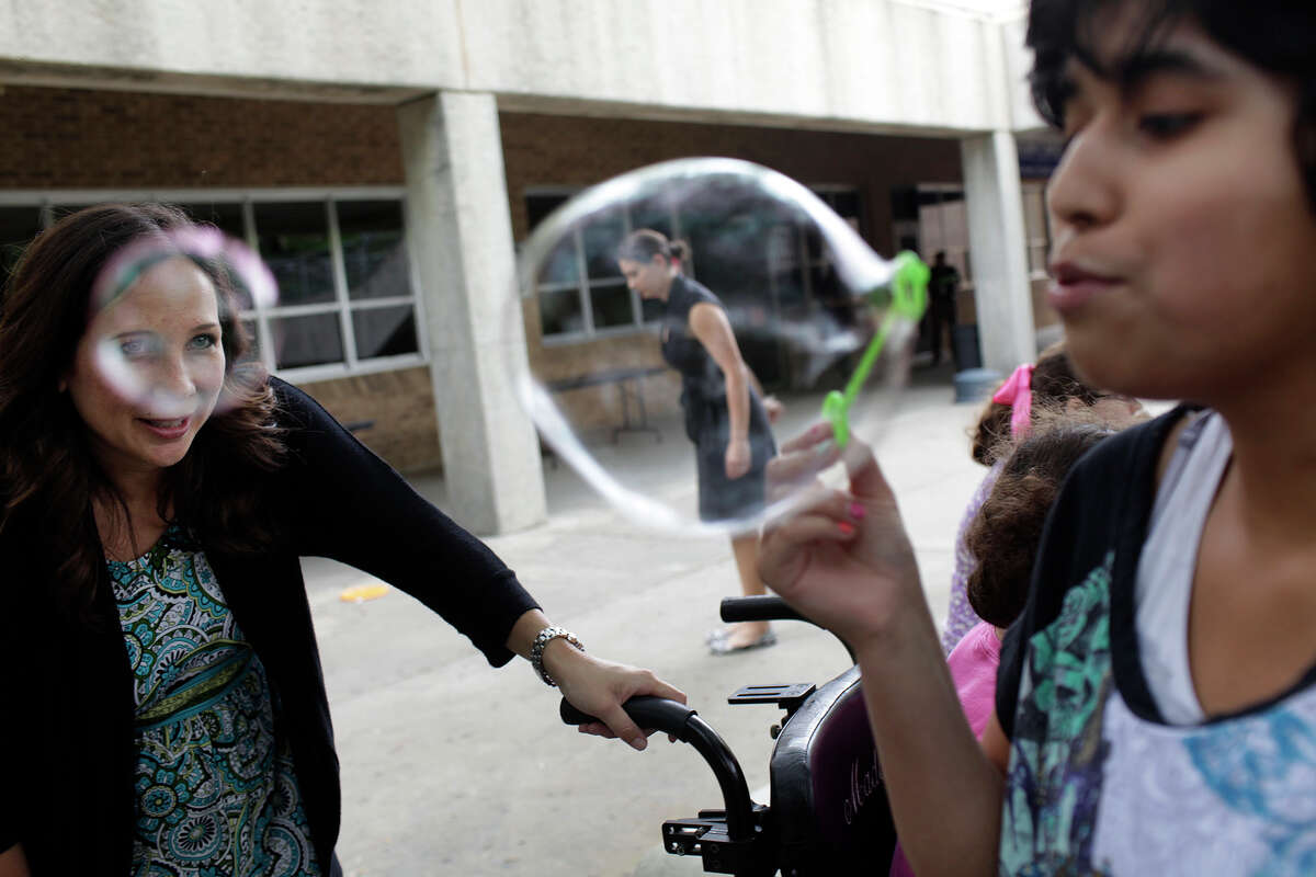 Karen Pumphrey, an award-winning special education teacher at Clark High School in the Northside Independent School District for the past 17 years, encourages student Chelsea Esquibel as she blows bubbles during class.