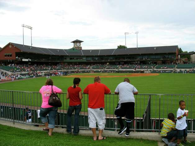 Fans watch pitchers warm up in the bull pen at Dickey-Stephens Park, home of the Arkansas Travelers minor league baseball team, in North Little Rock, Ark. Photo: Betty Luman / © 2012  Houston Chronicle