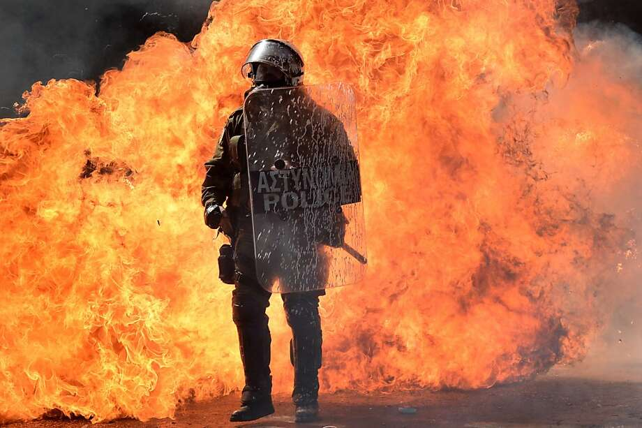 A fireball erupts behind a police officer after protesters hurled Molotov cocktails at security forces during a demonstration in Athens. Photo: Aris Messinis, AFP/Getty Images