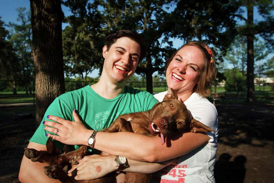 "Aldred Eckles, left, and Rhonda McManus hold their dog, Toby, who was recently adopted from BARC, Tuesday, Sept. 18, 2012, in Houston.  ""He looks like a pit bull mixed with a slinky,"" Aldred says. To win $100,000, BARC Animal Shelter & Adoptions needs to save the lives of at least 2,100 animals as part of the ASPCA's Rachael Ray $100K challenge.  ( Michael Paulsen / Houston Chronicle ) Photo: Michael Paulsen / © 2012 Houston Chronicle"
