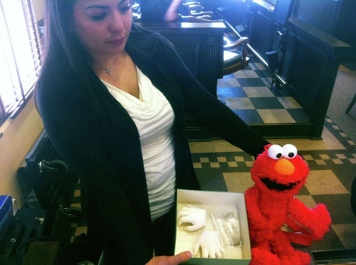Monica Meza. 35, holds the Elmo doll that belonged to her son Maddoux Cordova, and casts of his hands after testifying at a lawsuit trial. Maddoux, 22 months, died after he was administered morphine after a routine dental procedure.