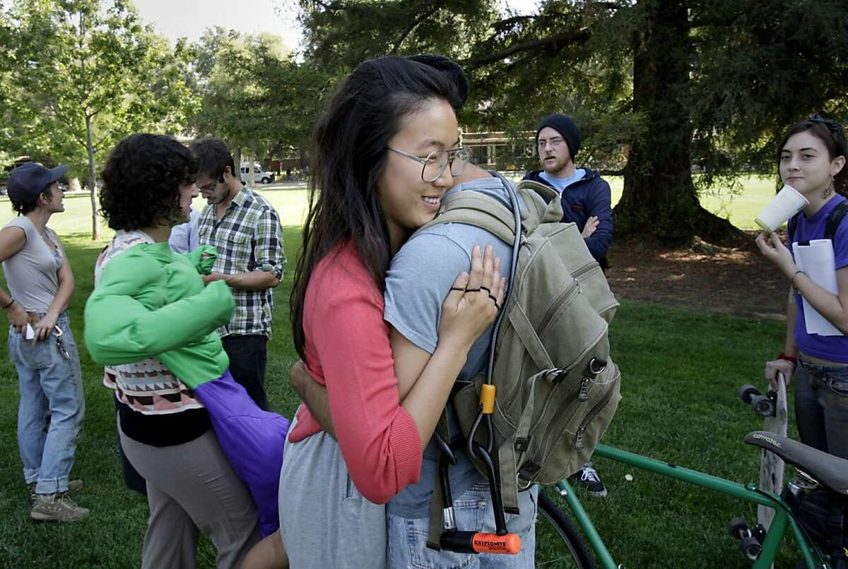Plaintiff Soo Lee (left center) hugged plaintiff Enosh Baker as other plaintiffs milled around after the press event at the Quad on the UC Davis campus. Attorneys for 21 UC Davis students and recent alumni announced a $1 million dollar settlement Wednesday September 26, 2012 because campus police doused the students with military grade pepper spray during a campus protest.