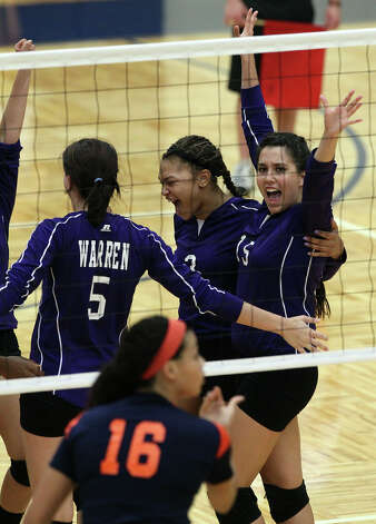Warren's Shaina Garza (15) celebrates with teammates Lauren McQueen (05) and Brittany Lawson (03) after a winning point against Brandeis in high school volleyball at Taylor Fieldhouse on Wednesday, Sept. 26, 2012. Photo: Kin Man Hui, San Antonio Express-News / ©2012 San Antonio Express-News