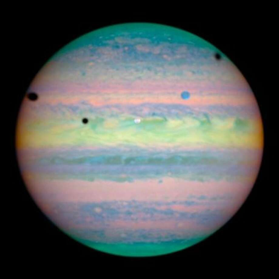 A near-infrared shot of Jupiter showing the shadows of three of its moons -- Io, Ganymede, and Callisto -- on the surface.