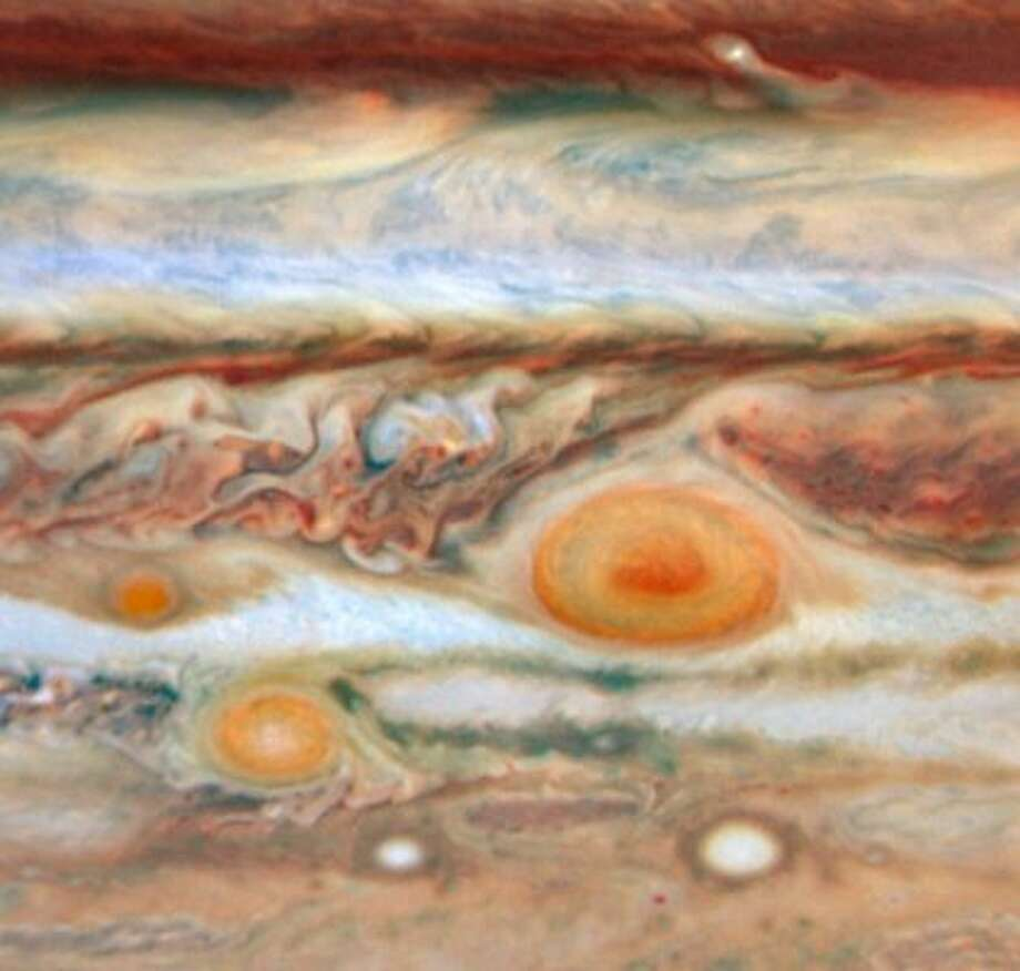 Back to Jupiter. This photo shows additional red spots, or swirling storms in the clouds of gas.
