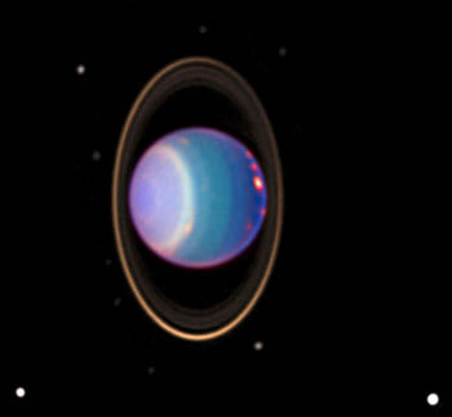 A daramatic view of Uranus, with storms raging on the surface, rings clearly visible and 10 moons orbiting the planet.