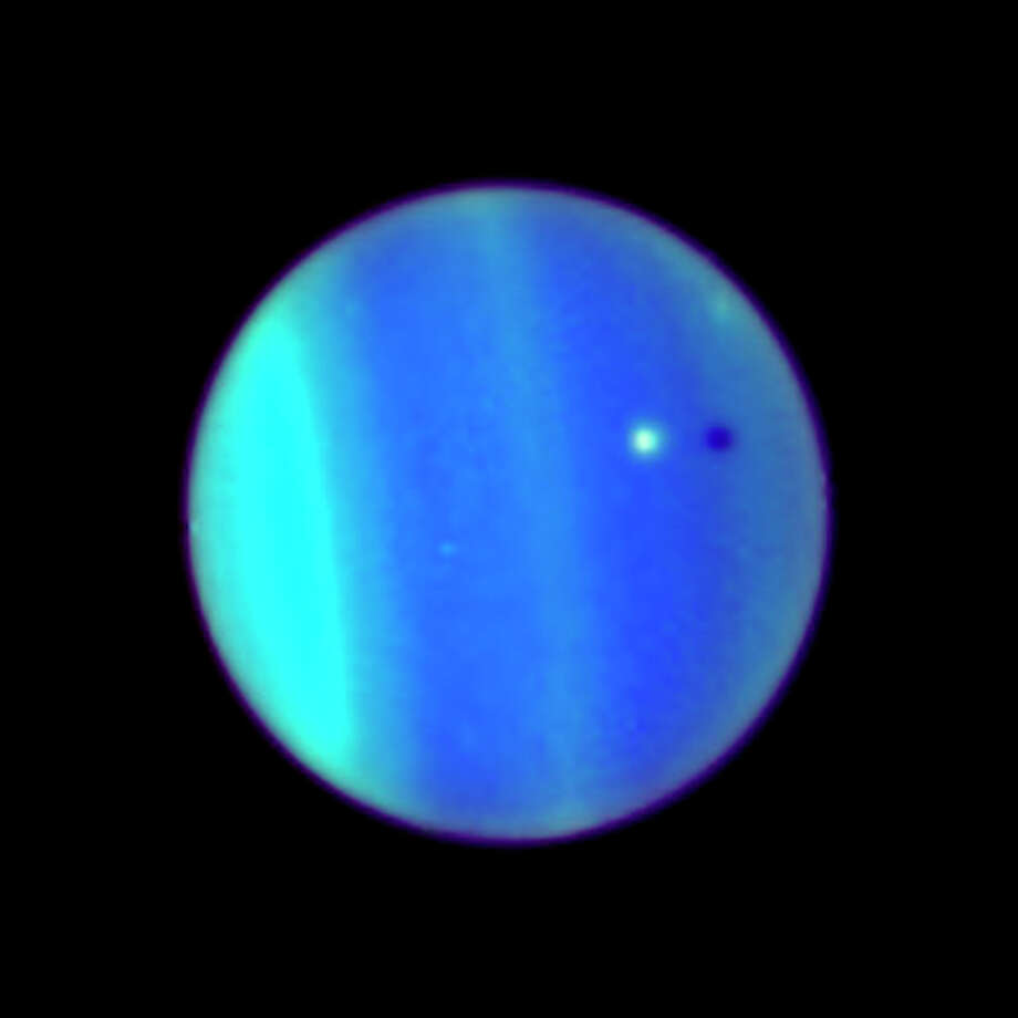 Uranus and its moon Ariel, casting a shadow on the planet.