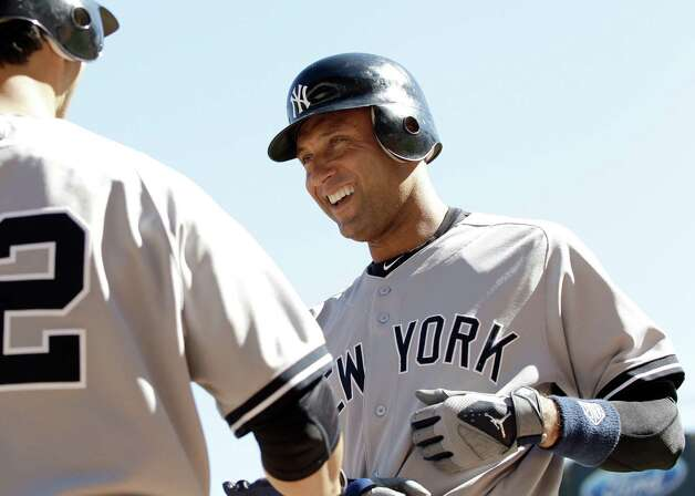 New York Yankees' Derek Jeter, right, is congratulated by Eric Chavez after he scored on a single by Nick Swisher off Minnesota Twins pitcher Brian Duensing  in the third inning of a baseball game Wednesday, Sept. 26, 2012 in Minneapolis. (AP Photo/Jim Mone) Photo: Jim Mone